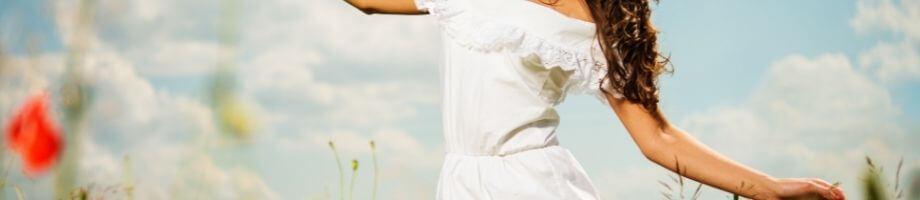 Kvinna på äng i vit långklänning